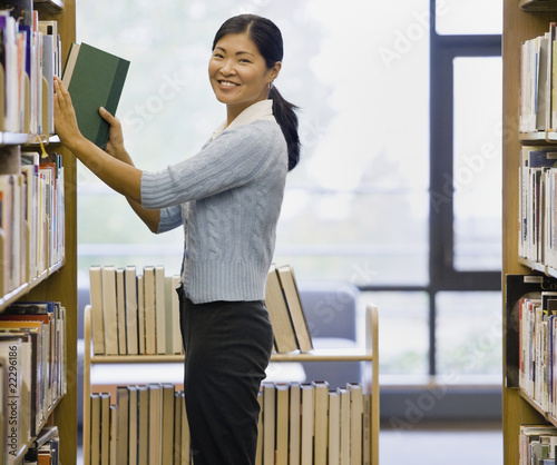 Asian woman shelving library books