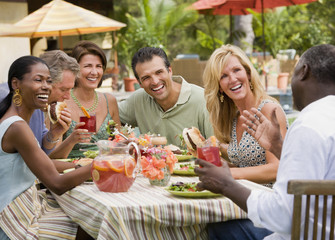 Multi-ethnic couples eating outdoors