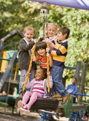 Multi-ethnic children playing on tire swing