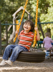 Asian boy sitting on tire swing