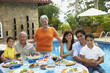 Multi-generational Hispanic family eating outdoors