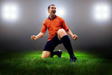 Happiness football player after goal on the field of stadium wit poster