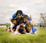 Multi-ethnic male soccer players in pile up