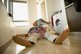 Man laying on floor under pile of laundry