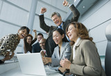 Multi-ethnic businesspeople cheering at laptop