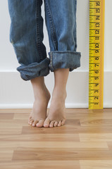 Boy standing on tiptoes next to ruler