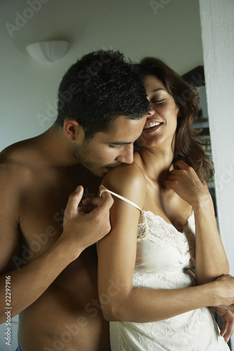 Hispanic man kissing girlfriend's shoulder