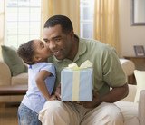 Mixed Race girl kissing father holding gift