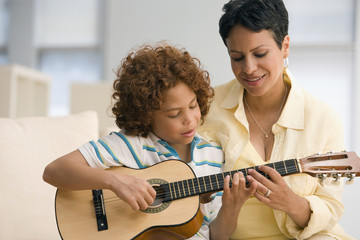 Mixed Race mother helping son play guitar