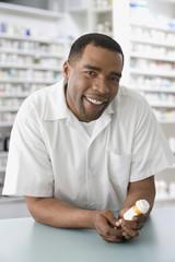 Mixed Race male pharmacist holding medication