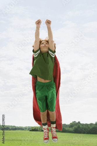 Mixed Race boy flying with towel as cape