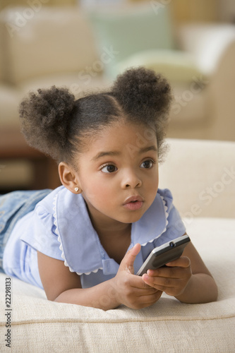 Mixed Race girl holding remote control