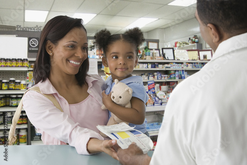 African mother and daughter getting prescription at pharmacy
