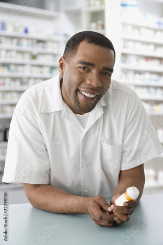 Mixed Race male pharmacist holding medication