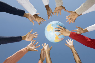 Multi-ethnic hands reaching for globe ball