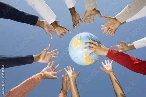 Multi-ethnic hands reaching for globe ball