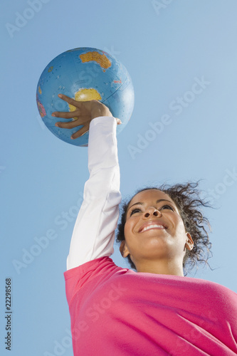 Hispanic woman holding globe ball
