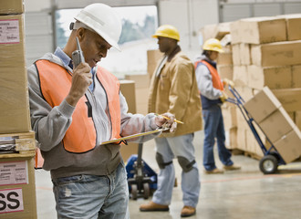 African warehouse worker talking on cell phone