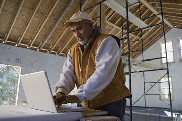 Hispanic architect typing on laptop