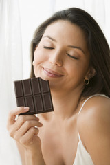 Hispanic woman eating chocolate bar