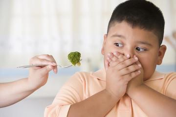 Hispanic boy covering mouth next to broccoli