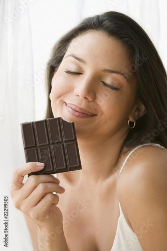 Hispanic woman eating chocolate bar