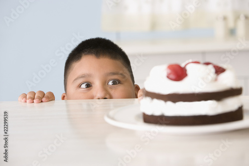 Hispanic boy looking at cake