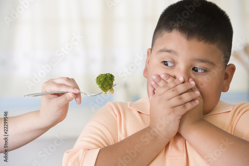 Hispanic boy covering mouth next to broccoli