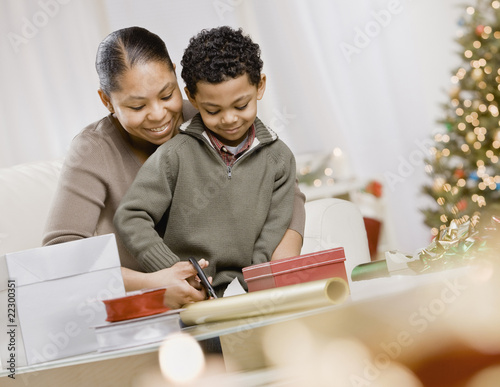 Mixed Race mother and son wrapping Christmas gifts