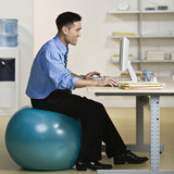 Asian businessman sitting on exercise ball
