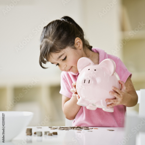 Indian girl holding piggy bank