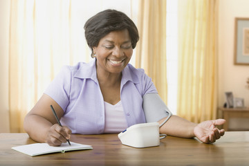 Senior African woman taking own blood pressure