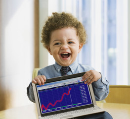 Mixed Race baby holding laptop with graph