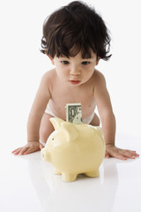 Hispanic baby looking at money in piggy bank