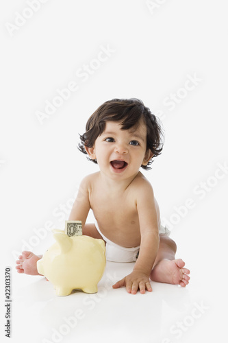 Hispanic baby next to piggy bank