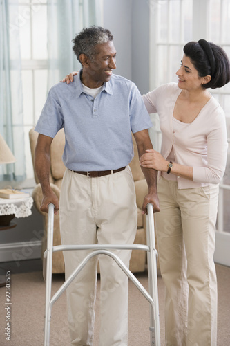 Middle Eastern woman helping man use walker