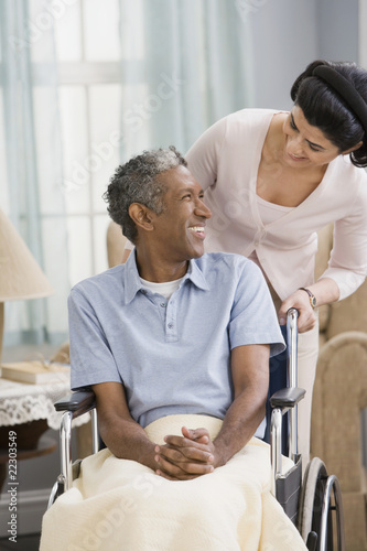 Middle Eastern woman smiling at man in wheelchair