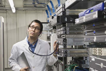 Asian man listening to computer server with stethoscope