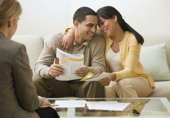 Hispanic couple holding brochures and hugging