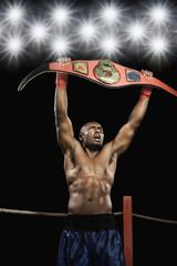 African boxer lifting championship belt