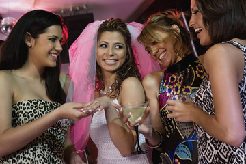Friends admiring womanÕs engagement ring in nightclub