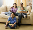 Hispanic family watching television in living room