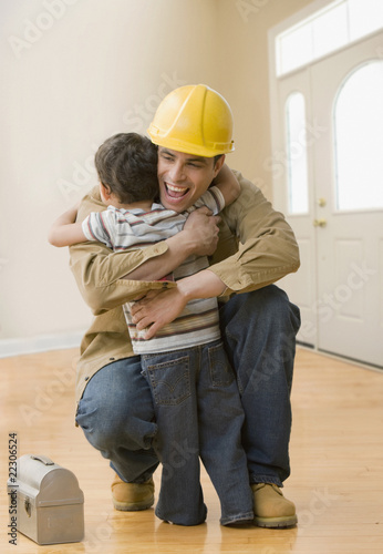 Hispanic construction worker hugging son
