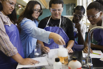 Students and teacher performing experiment in chemistry lab