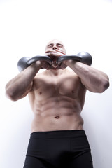 Young attractive man in gym working with kettlebells