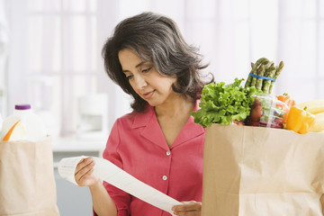 Hispanic woman checking grocery receipt