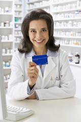 Hispanic pharmacist holding insurance card