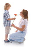 boy bringing a bunch of flower to mom
