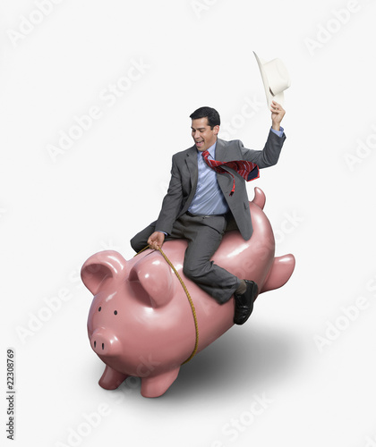 Hispanic businessman riding piggybank