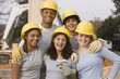 Volunteers wearing hard-hats posing at construction site
